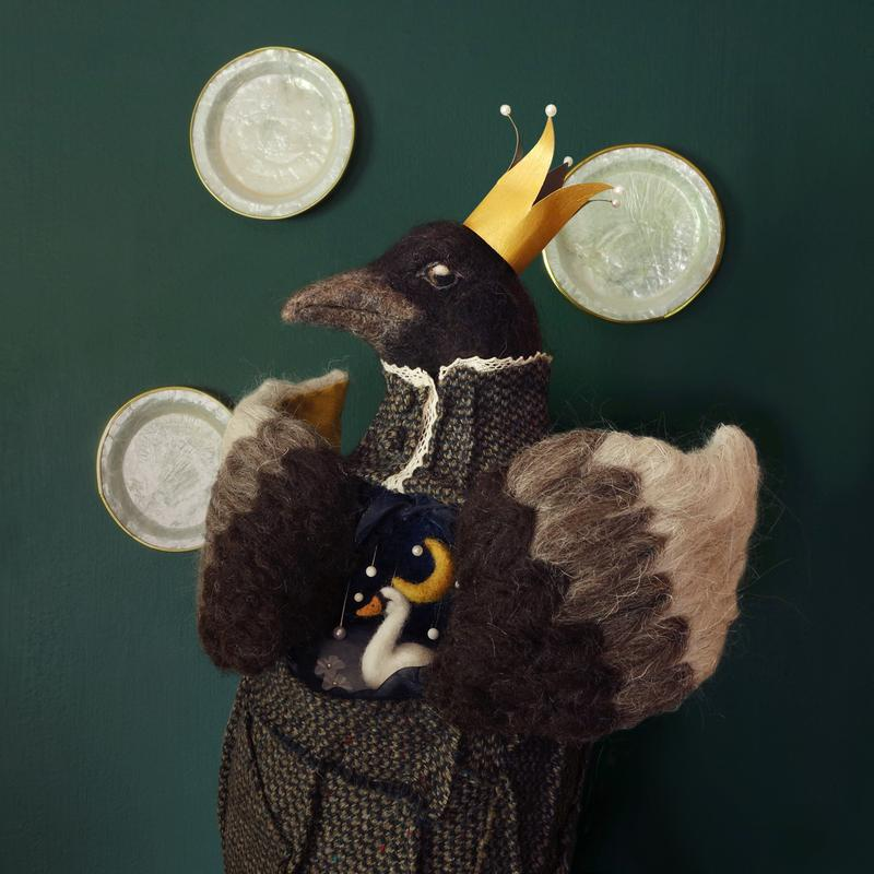 A needle felted anthropomorphic sculpture of a raven wearing a gold crown, inside the raven's body a miniature scene of a swan under a night sky.