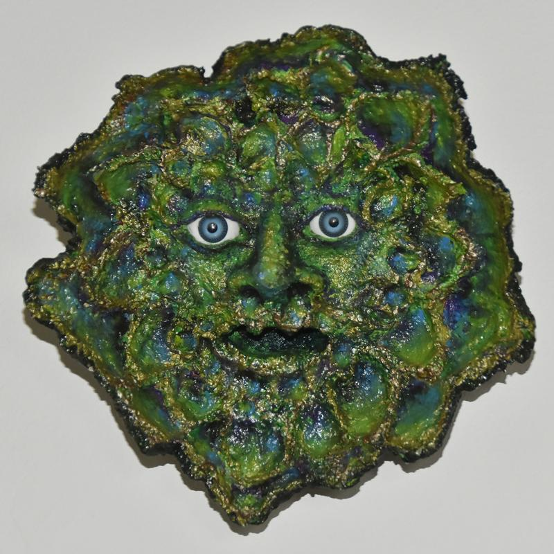 Papier-mache sculpture of open-mouthed blue-eyed face surrounded with irregularly contoured and roughly textured leaves, painted in greens and blues with accents of bronze and gold.