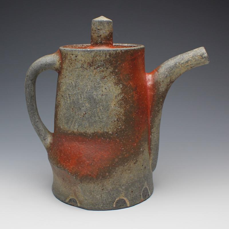 A wheel thrown and altered lidded coffee pot with deep orange and grey blushing.