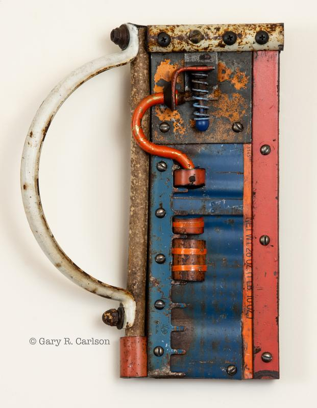 A design of colored metal shapes using found objects. A vertical blue area bordered with orange and red-orange lines of metal attached with round head screws that make a pattern of dark dots. A small blue spring is held in place with an orange pipe in the shape of a ?. A big rusted white handle creates a negative space on the left side.