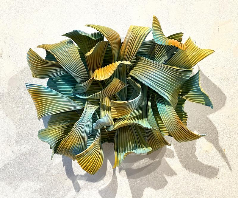 An organic wall sculpture made of aluminum and encaustic paint (beeswax) relating to plants and flowers.