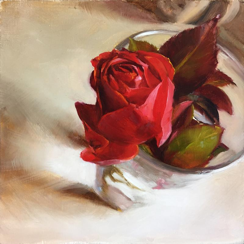 A painting of a deep red rose in a drinking glass on a kitchen counter top viewed from above. The late afternoon light is shining through the glass and lighting up the surface of the counter. The folds of the rose are rich in color and the shadows between the petals seem to draw you into the rose.