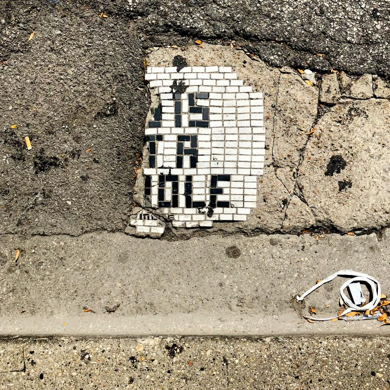 """Partial mosaic of text which once read, """"This is not a hole."""" Depicted as found on Michigan Avenue, Chicago, IL."""