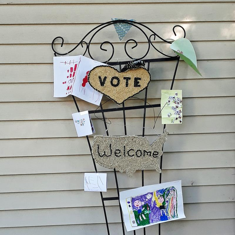 A display of heart shaped crop art with the word VOTE spelled out in black beans, children's art and another crop art in the shape of the United States with the word WELCOME.  On the top of the heart is a visiting live  woodpecker, getting a snack.  All the art is on a garden trellis.