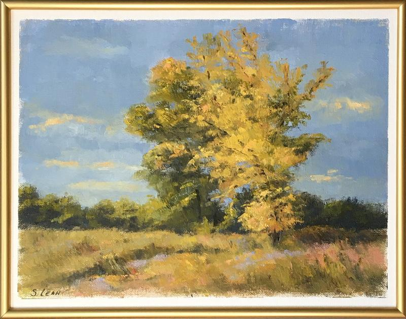 Set against a dark blue sky, this painting of trees in a grassy field captures the landscape transitioning from verdant green to gold and copper as the landscape absorbs the final days of summer.