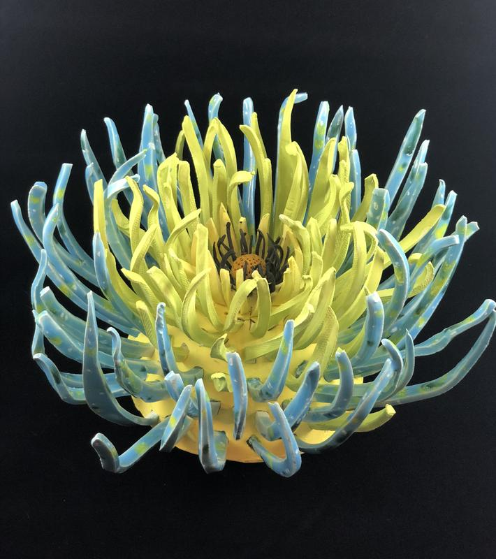 A dimensional Ceramic flower inspired by ocean plants with individually handcut petals arranged to create movement within the piece.