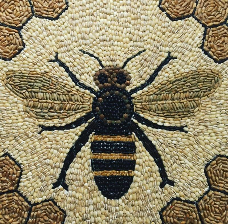 An mosaic image of a bee created with seeds and grains in the center of a canvas board. It is natural colored with black, cream, and tan tones. The corners of the piece feature a honey comb motif.