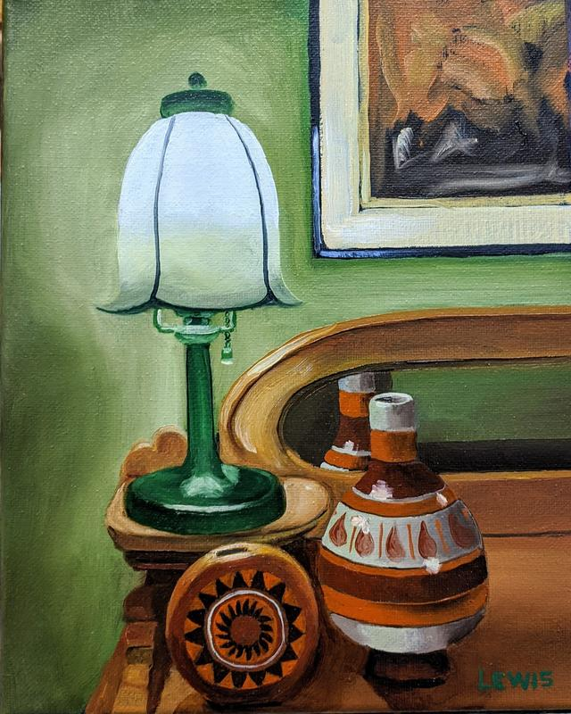 Small white globed desk lamp with a green base sitting on a desk illuminating 2 southwestern pieces of pottery. The small pottery are reflected in the mirror of maple colored desk. Behind the desk is an abstract painting hanging on a green wall.