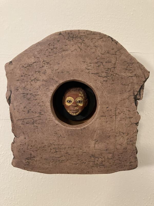 Ceramic, domed frame with circular window revealing a realistic, sculpted head with decorated face within.
