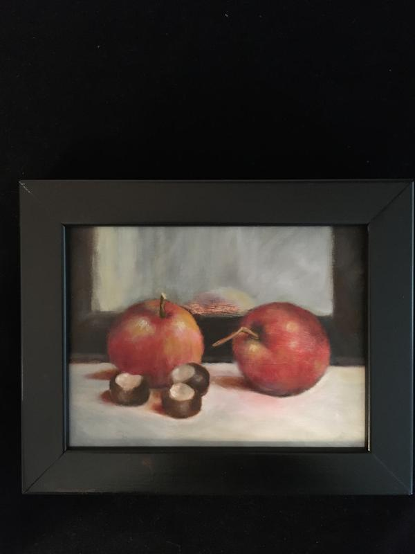 A still life painting of two Haralson apples and three Horse Chestnuts on a linen cloth, in front of green curtains and a mirror.