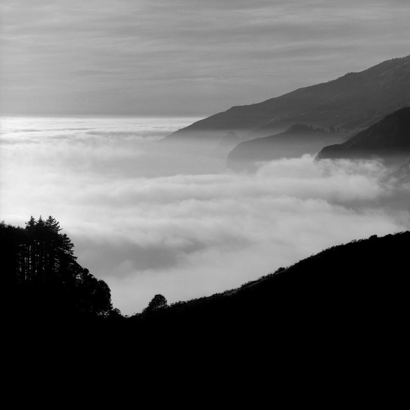 Black and white photograph of a highway obscured by fog in Bug Sur, California