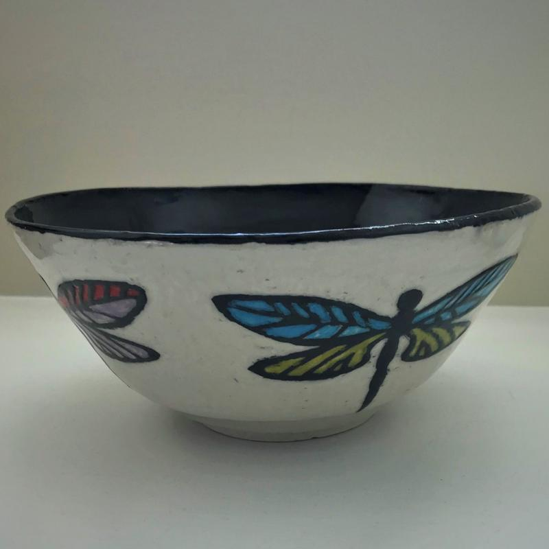 A sgraffito style white clay bow with a black inner surface. Vertical dragonflies adorn the outside of the bowl with colorful wings in blue and green and purple and red.