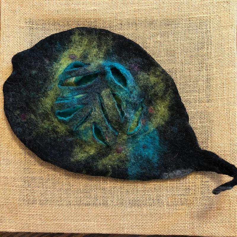 """A 3-dimensional wet-felted fish treated with many layers of Norwegian wool roving. A plastic resist was placed in the center of the shape about halfway through the felting process so that it could be cut to reveals the """"insides"""" of the fish."""