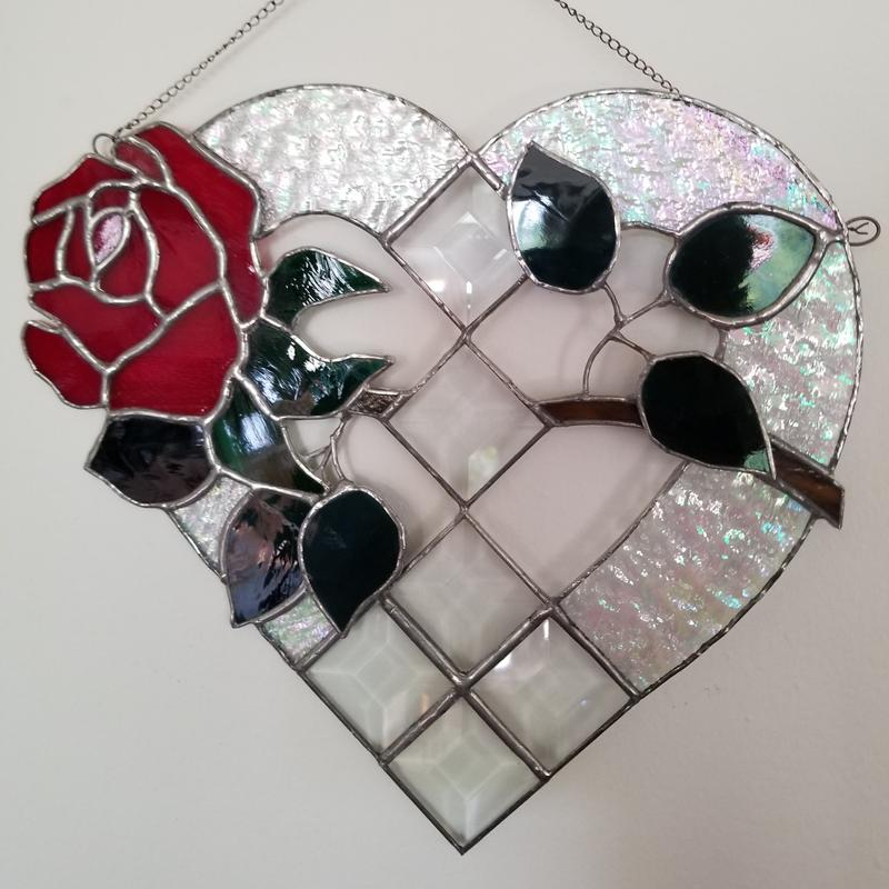 A beautiful red rose with green glowing leaves interweaves through the center of an iridescent heart with diamond shaped bezels.