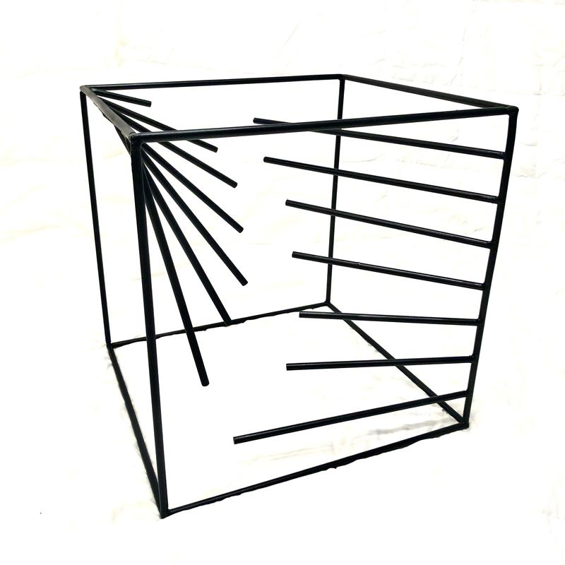 A cube of steel rods with steel rods welded on the inside of 2 opposite edges, extending into the cube, their ends describing a negative space in 3 dimensions, painted flat black.