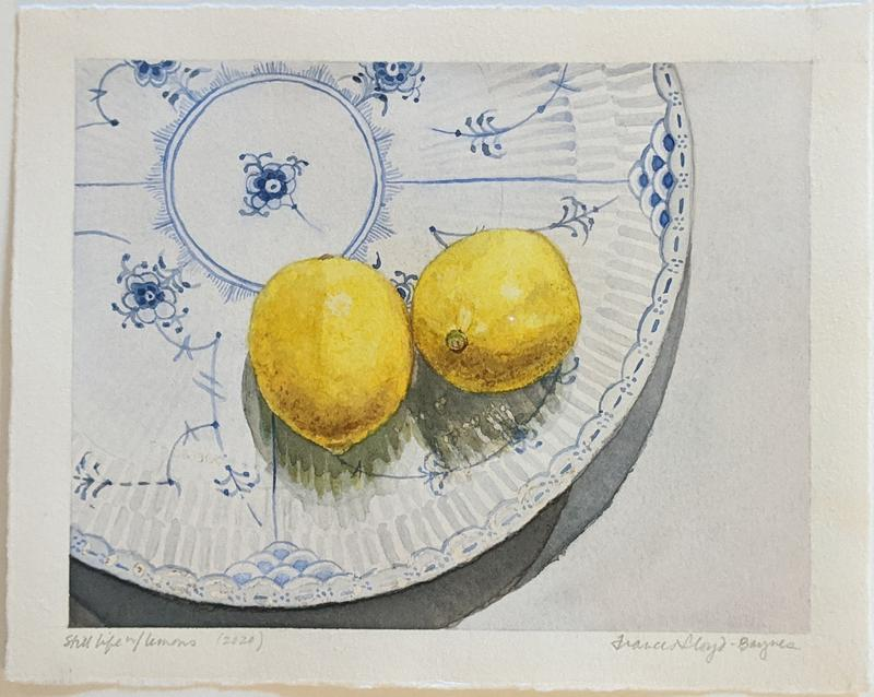 Two lemons sit on a blue and white porcelain plate
