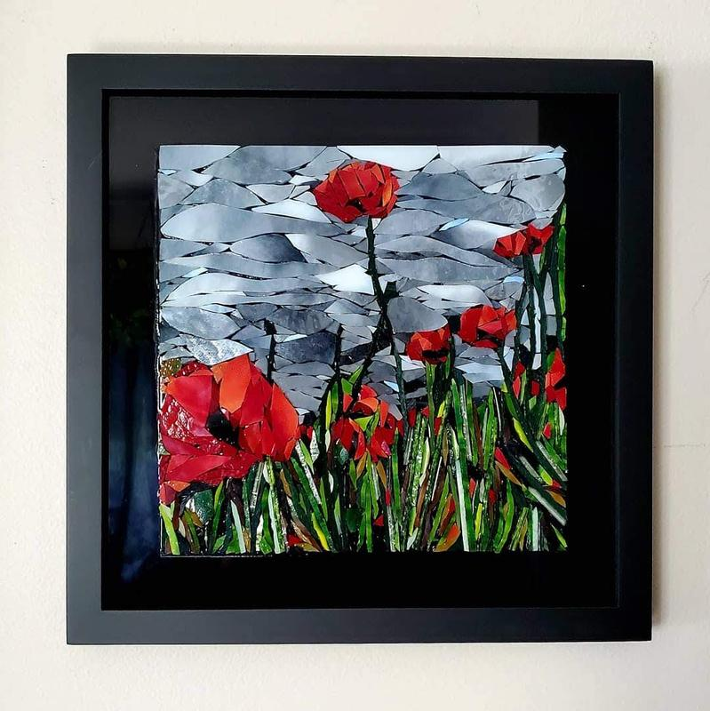 Imagine if someone could paint with hand cut glass.  This is a stained glass mosaic of a handful of bright red peonies, reaching upwards towards sunlight, underneath a stormy iridescent gray sky.  The stems of the flowers are long, flat pieces of glass, as well as some pieces of glass turned on their sides that catch the light just so.
