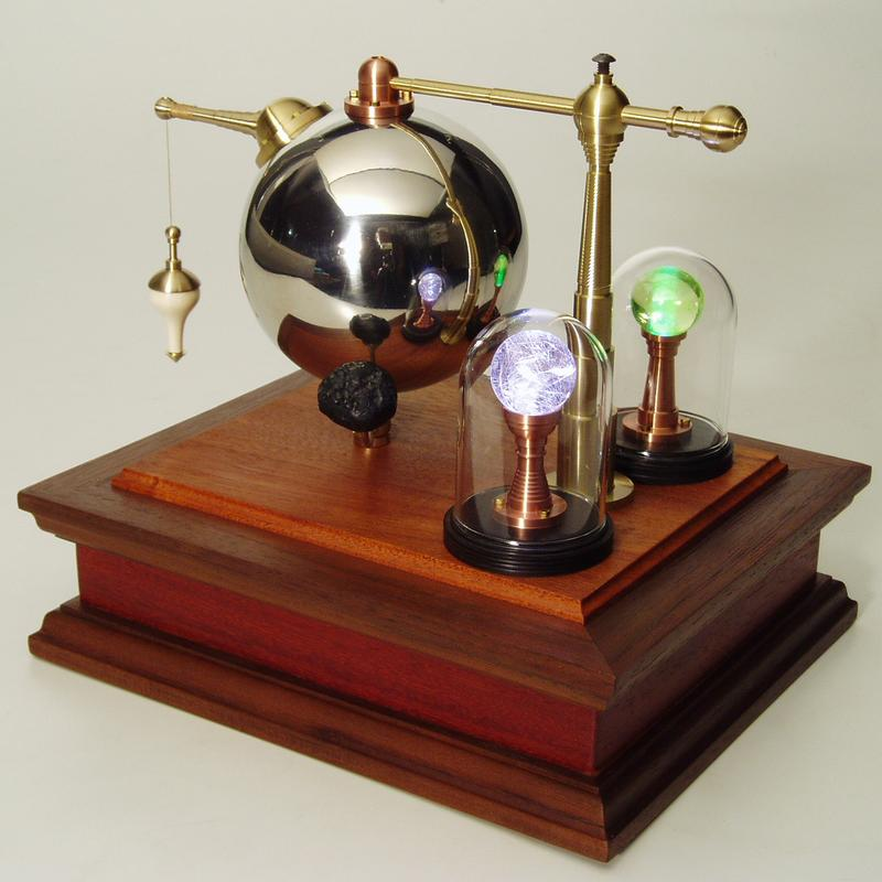 """Based in the tradition of the Philosophical Instrument this work, a Conundra Object, is based upon an extraction of Kepler's solar system model and a musing of what existed beyond his platonic """"Celestial Spheres"""".  Kepler's chrome sphere is supported by hand machined brass and copper supports with a plumb bob centered on space, flanked by illuminated display spheres under glass, circled by a rotating planetoid form, all mounted to a box base of various hardwoods."""