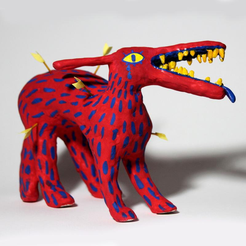 A sculpture of a red, dog-like creature with dark blue hatch-marks imitating fur along its entire body. The creature's snout is long, and its mouth is open, revealing yellow teeth and a lolling dark blue tongue. It's body is pierced by arrows and there are dark blue tears falling from its yellow eyes.