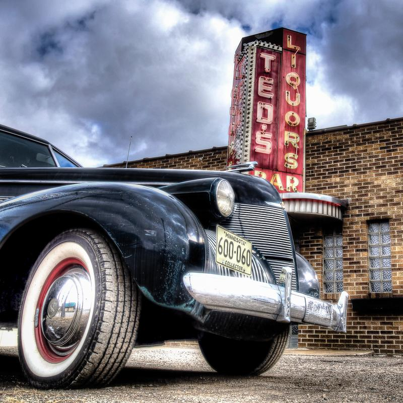 """Classic Cadillac parked outside of Ted's Liquors in Saint Paul, Minnesota. The red neon """"Ted's Liquors sign and building can be seen next to the car"""