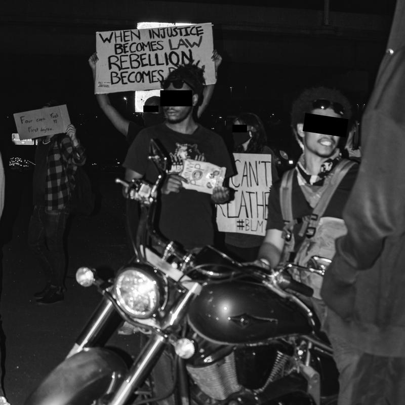 """A motorcycle and two people are in focus partaking in a protest in Minneapolis Minnesota, other protester's signs read """"WHEN INJUSTICE BECOMES LAW, REBELLION BECOMES DUTY"""", and """"I CAN'T BREATHE #BLM"""". Image is in black and white with protester's face blocked out to protect identity"""
