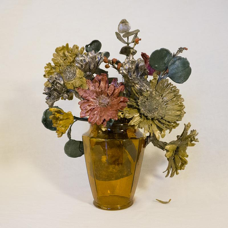 A sculpture of cast aluminum flowers finished with vibrant India ink in shades of yellow, green and red arranged in amber glass vase