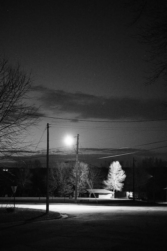 A black and white image, shot at dusk, picturing a rural street corner with a lamp pole shimmering down on a empty corner. The light illuminates a rural house and a tall pine tree. Power lines can be seen zip-zagging across the murky gray sky. The clouds hang low in the photo, as the sky takes up much of the image.