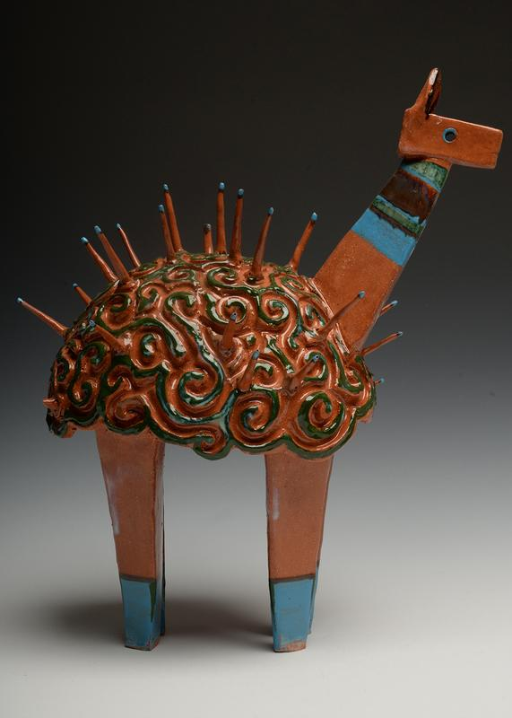 A soft alpaca made of red clay standing on 4 long triangular legs and a long triangular neck. the fur texture is made of swirls that have spikes coming out. the animal looks stoic and is embellished with blue, black and green glaze. it looks very enticing to touch.