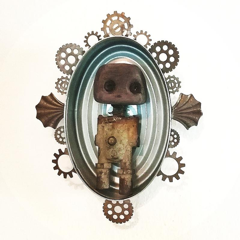 A small oval tin shrine surrounded by aged metal gears with a robot made of found parts inside.