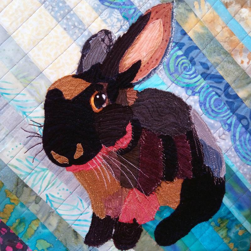 A portrait of a friend's pet rabbit, a mixed media creation, started with a photograph, then little pieces of brightly colored fabric fused and sewn onto a contrasting diagonal background.