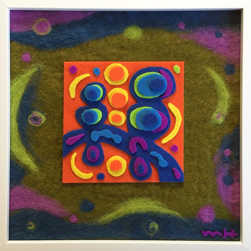A felt artwork with bright fluorescent hand cut abstract shapes in the center, surrounded by swirling needle felted shapes and background using muted colors and a softer focus.