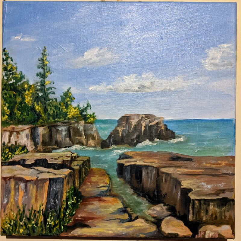 A painting of rocky shore at Grand Marais, Lake Superior. Multicolored, flat faced rocks jutting out into the blue lake with some tree growth.