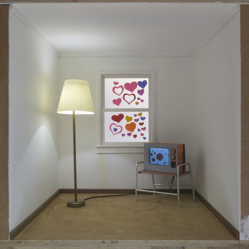 A one-eighth-scale diorama of a carpeted living room. A miniature floor lamp lights the interior and a miniature tv displays an image of the COVID-19 virus. There is a window covered with colorful paper hearts taped to the glass.