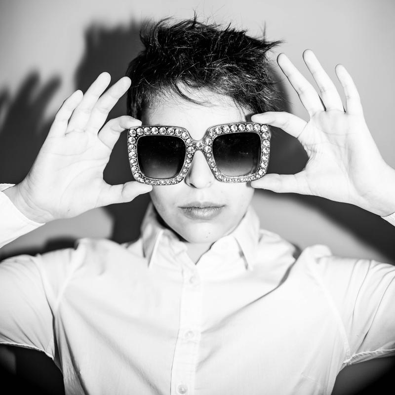 A black and white portrait featuring the subject in a white shirt and giant sunglasses.