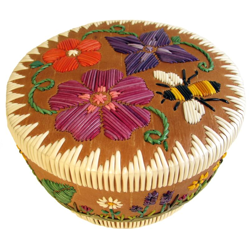 A rounded box rimmed with white porcupine quills and decorated with colored porcupine quills that are in the shapes of flowers with leaves, stems and vines.