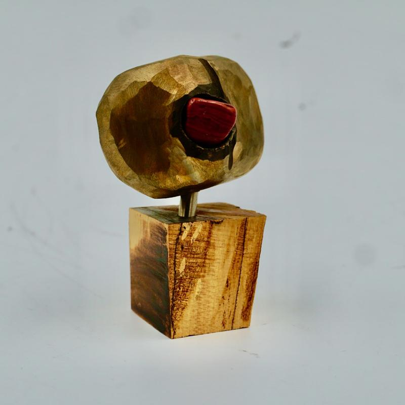 A former cube of bronze, hammered & scraped into a softer form, drilled into to insert one mesmerizing deeply red stone eye, balanced upon a contradictorily slim stem above a singed hardwood block base.