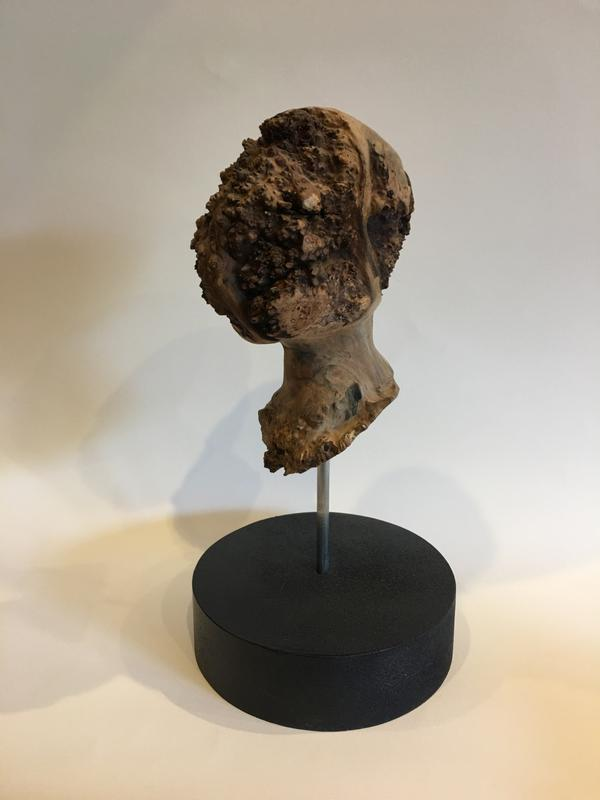 Wood carving of the artist's head from found materials.