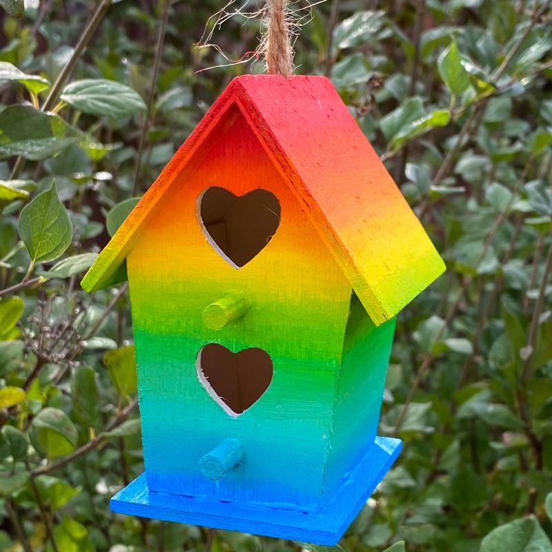 A small birdhouse with two heart openings painted with a rainbow that blends from red through blue in front of green lilac bushes.