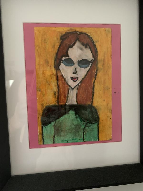 A colored paste of my mom. Red hair blue glasses a black cape over a green shirt. Pointy chin. Long neck.