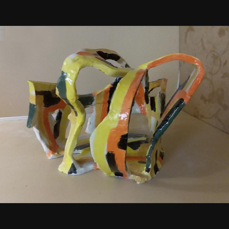 Ceramic piece made from slabs of clay, with lots of negative space. Glazed with yellows, orange, green, and black.
