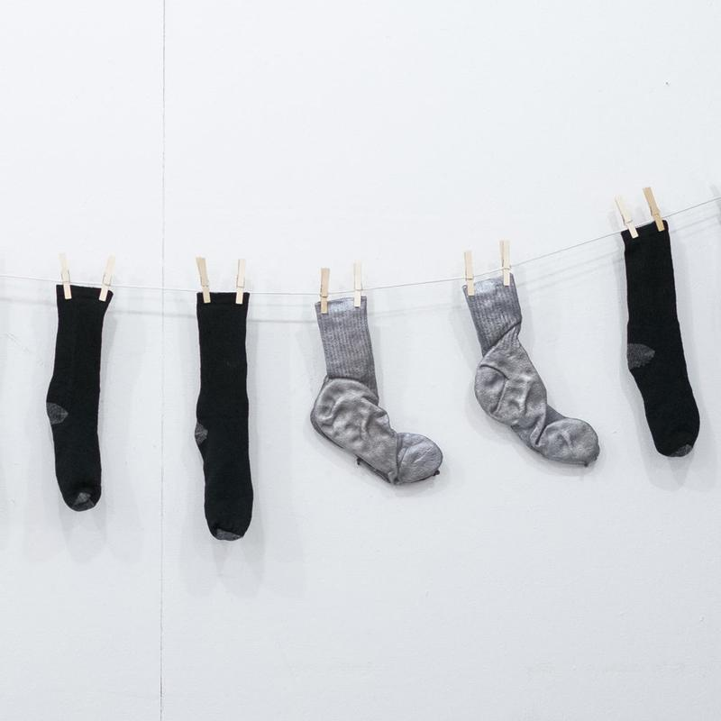 Photograph of sculpture. Clothes line with black socks weighed down by cast aluminum socks on a white background.