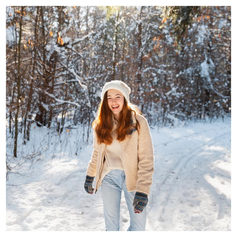 a young auburn-haired woman, mid laugh, standing in the middle of a snowy forest in northern Minnesota.