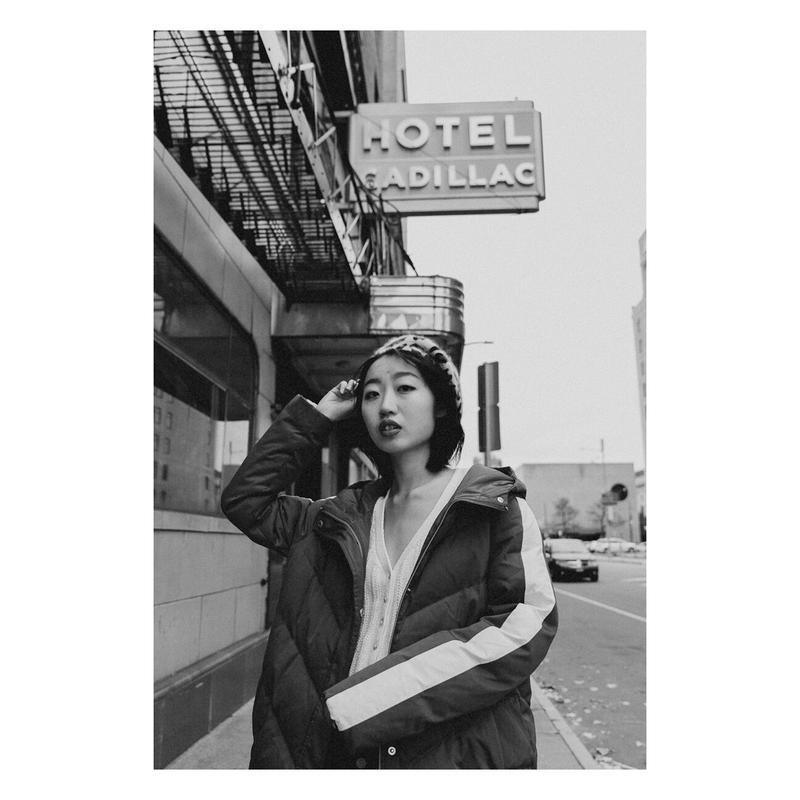 Black and white photograph of a girl wearing a winter coat and a beret in front of an old hotel called Hotel Cadilllac.