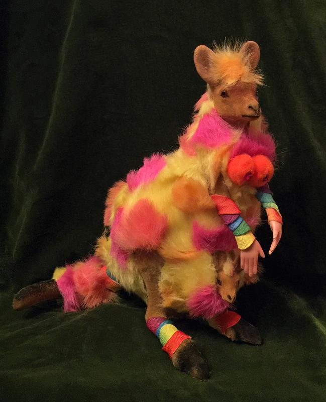 An 11-inch tall toy Mama Kangaroo (with Joey), augmented with human hands, and candy-colored fun fur - with a dark, Rembrandt-esque green velvet background.