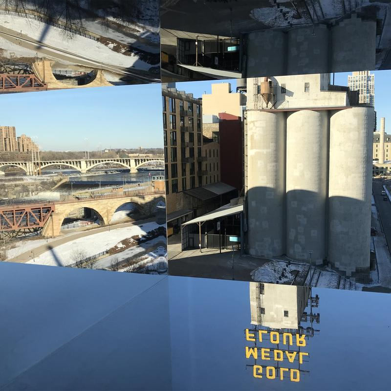 A view through a window that's surrounded by mirrors overlooking the Mississippi the Mill District.