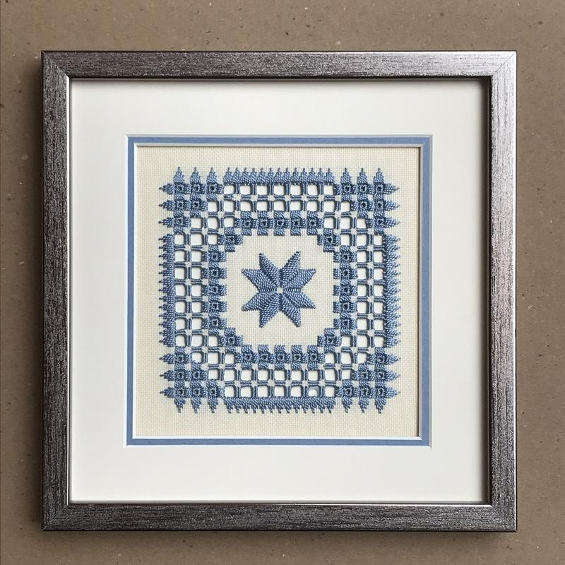 Silver framed, white/light blue matted, Hardanger Embroidery, stitched with soft blue threads on Ada cloth, the eight-pointed star is surrounded with a complimenting embroidered design of circles and points.