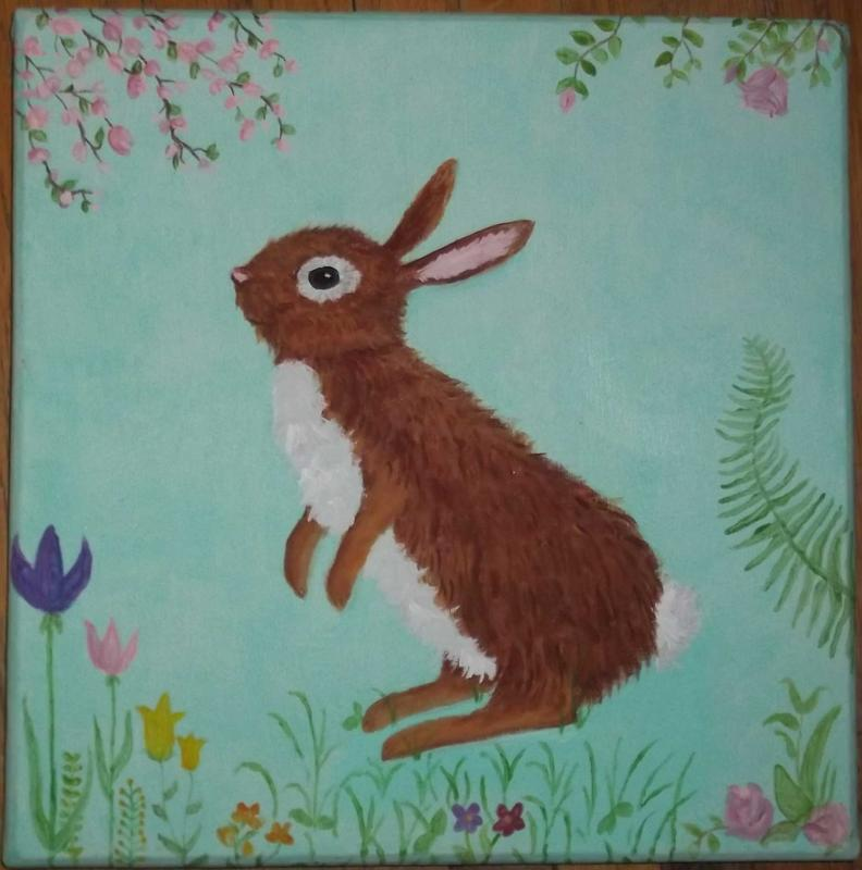 Little brown bunny surrounded by flowers and other plants.