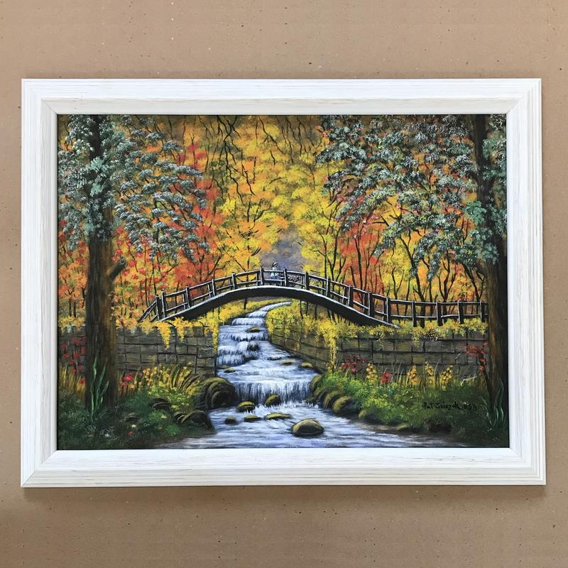 White wooden framed, acrylic painting of autumn's beauty - wandering stream over rocky waterway centers the image's story of two people crossing over on a dark, white highlighted foot-bridge, surrounded with mossy flowers in the foreground embracing greens, oranges, yellows creating leaves of the changing season's trees.