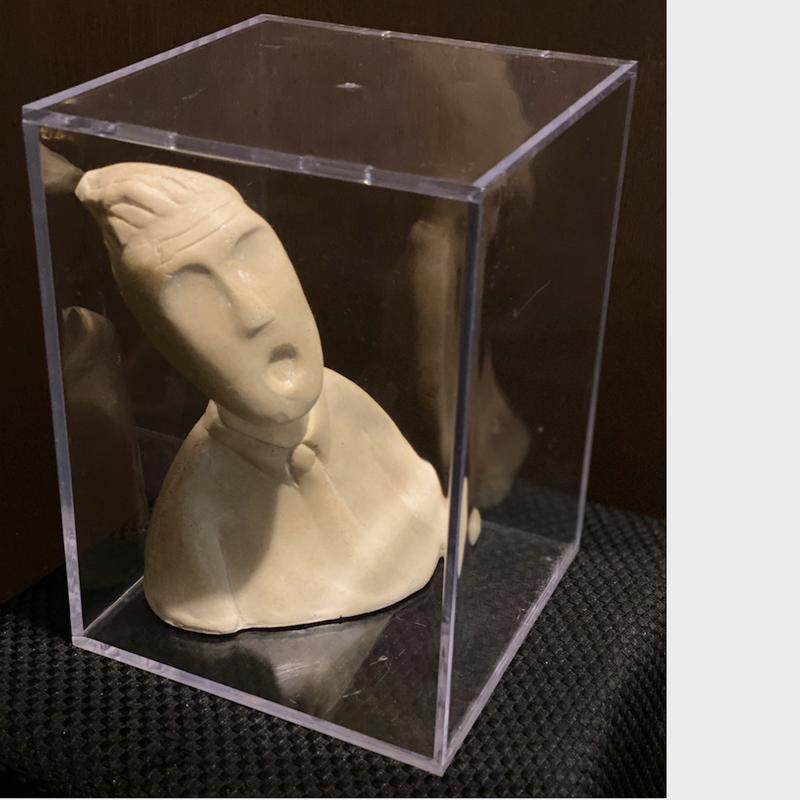 A cream colored sculpture of a man tortured by a sense of confinement screams silently. His eye sockets, empty, like his suffering soul. The clear box he lives in, an almost invisible cell, suffocates his aspirations.