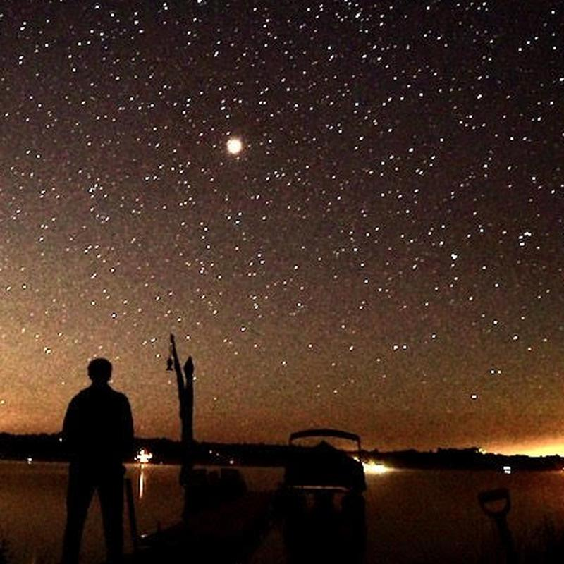 A man standing at the edge of a silhouetted lake star gazing on a north night.